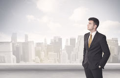 Sales person talking in front of city scape. A young adult businessman standing in front of city landscape with skyscraper buildings and clouds concept Royalty Free Stock Images