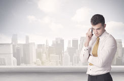 Sales person talking in front of city scape. A young adult businessman standing in front of city landscape with skyscraper buildings and clouds concept Stock Photos