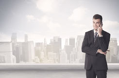 Sales person talking in front of city scape. A young adult businessman standing in front of city landscape with skyscraper buildings and clouds concept Stock Image