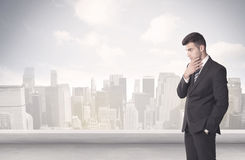 Sales person talking in front of city scape. A young adult businessman standing in front of city landscape with skyscraper buildings and clouds concept Stock Photo
