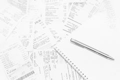 Sales receipts with notebook and silver pen, EET evidence. Paper cash register receipts in a lose pile close up. EET evidence in Czech republic Stock Photo