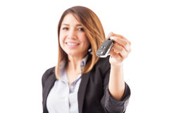 Sales rep handing over some car keys. Closeup of a young female sales executive handing over some car keys to a customer. Focus on keys stock images