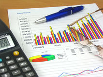 Sales Report 2. Colorful sales charts, calculator, blue pen and glasses Royalty Free Stock Images