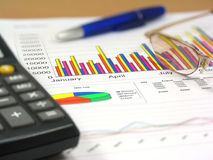 Sales Report 4. Colorful sales charts, calculator, blue pen and glasses. Shallow DOF, focus on charts Stock Image