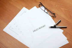 Sales report. Glasses and pen Stock Image
