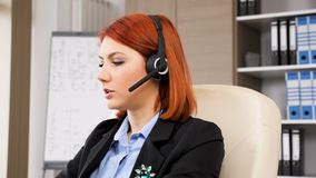 Sales representative with a headphones set on talking. To the customers stock video footage