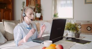 Sales representative in headset speaking to client and making video conference call on laptop.