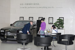 Sales representative introducing a luxury Ghost from Rolls Royce to a lady Stock Images