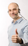 Sales representative man with an headset. Shows his thumb up Royalty Free Stock Photos