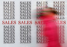 Sales shopping. Person passing by a sales window shop in the discounts season stock image