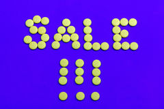 Sales sign dressed with yellow candies Stock Images