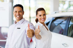 Sales staff dealership. Portrait of sales staff with thumbs up at a car dealership Royalty Free Stock Photography