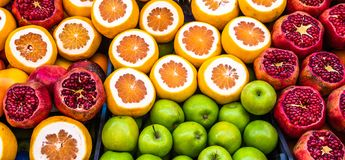 Sales stand for juice of apples, oranges and pomegranates with sliced fruits stock photo