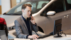 Sales talking on phone while using computer. At desk in car showroom Stock Photography