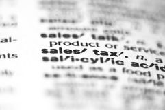 Sales Tax. Extreme macro or close up of the word Sales Tax. Very shallow depth of field is intentional and shows only the word sales tax in focus Royalty Free Stock Photo
