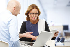 Sales team. Consulting while sitting at office and using laptop and digital tablet royalty free stock photography