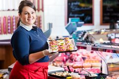 Sales woman in butcher shop offering finger food stock photos