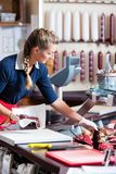 Sales woman in butcher shop putting different kinds of meat in display royalty free stock photos