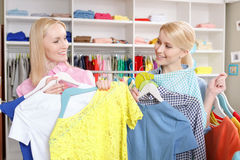 Sales woman and a customer with hangers Royalty Free Stock Image