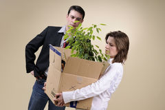 Sales woman leaving office with box. White upset woman leaving her business life and upset manager in background Stock Photo