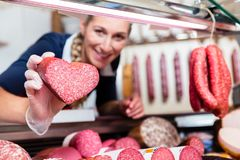 Sales woman in meat shop showing a heart shaped sausage. To customer Stock Photography