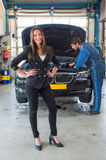 Sales woman standing in front of a car, being serviced for deliv. Car sales woman, standing in front of a used car, which is serviced by a mechanic, ready to be Royalty Free Stock Image