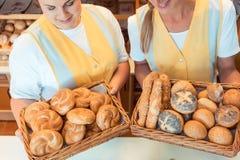 Sales women in bakery presenting fresh bread. In a basket stock photo