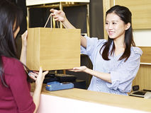 Salesclerk handing merchandise to customer. Young female asian salesclerk handing a paper bag of merchandise to a customer at the check-out counter Royalty Free Stock Photography