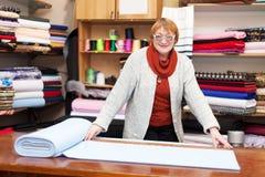 Salesclerk measures the fabric Royalty Free Stock Photo