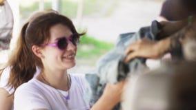 Saleseman дает куртку джинсовой ткани к молодой счастливой женщине в розовых солнечных очках акции видеоматериалы