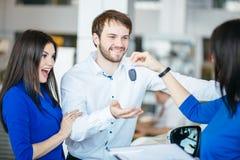 Salesgirl автомобиля давая ключ нового автомобиля к привлекательным предпринимателям пар Стоковые Фотографии RF