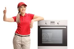Salesgirl leaning on an electrical oven and giving thumb up stock photography