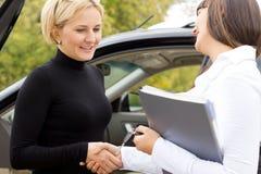 Saleslady που συγχαίρει έναν νέο ιδιοκτήτη αυτοκινήτων Στοκ εικόνα με δικαίωμα ελεύθερης χρήσης