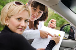 Saleslady assisting a customer to buy a car. Saleslady leaning through the open window of a car assisting female customer to buy car pointing to  contract Royalty Free Stock Photos