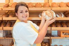 Saleslady in bakery shop presenting bread. To potential buyer Stock Photos