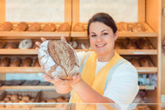 Saleslady in bakery shop presenting bread. To potential buyer Stock Photography
