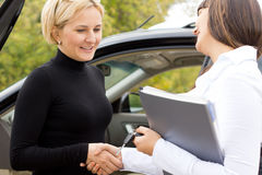Saleslady congratulating a new car owner. Shaking hands and smiling with an attractive blond women as they finalise the deal Royalty Free Stock Image