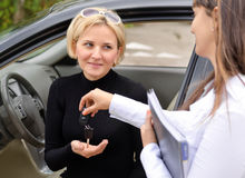 Saleslady handing over the keys. To an attractive blond women who is now the proud owner of a new car Royalty Free Stock Photography