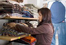 Saleslady in a jeans wear shop. A shop assistant putting clothes on the shelves Royalty Free Stock Photos