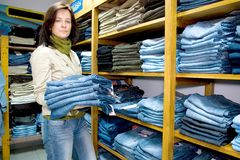 Saleslady in a jeans wear shop. The saleslady holding a few pairs of blue jeans, shelves with lots of them Stock Photos