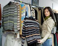 Saleslady in a jeans wear shop. The saleslady showing one of the many sweaters Royalty Free Stock Photography