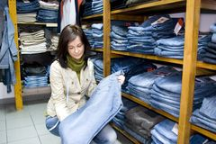 Saleslady in a jeans wear shop. The saleslady with a metering tape holding a pair of blue jeans, shelves with lots of them Royalty Free Stock Photography