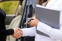 Saleslady selling a car and shaking hands Stock Photo