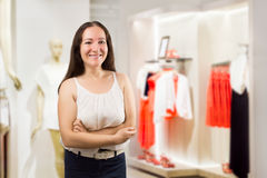 Saleslady smiling. Happy saleslady standing at the boutique Royalty Free Stock Photo