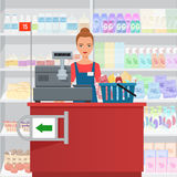 Saleslady woman cashier standing at checkout in supermarket. Royalty Free Stock Photography