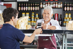 Salesman Accepting Mobile Payment From Customer In Cheese Shop royalty free stock image