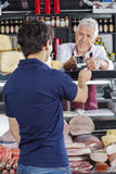 Salesman Accepting Payment From Customer In Cheese Shop Royalty Free Stock Image