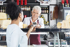 Salesman Accepting Payment From Customer In Cheese Shop. Smiling salesman accepting payment from customer through credit card in cheese shop Royalty Free Stock Image