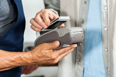 Salesman Accepting Payment Through NFC Technology Royalty Free Stock Photo