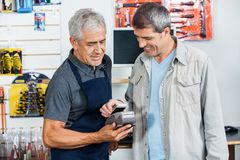Salesman Accepting Payment Through NFC Technology. Portrait of senior salesman accepting payment through NFC technology from male customer in hardware store Royalty Free Stock Image